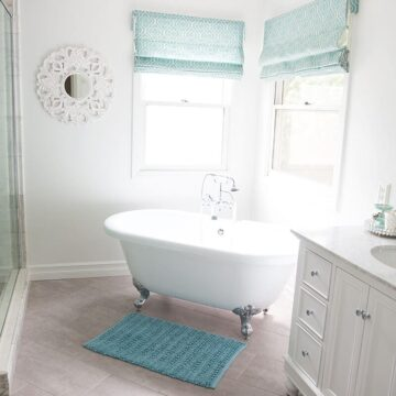 Bathroom makeover via I Heart Naptime: Grey and white bathroom remodel with Carrara marble herringbone tile tile, white vintage tub and blue accents.
