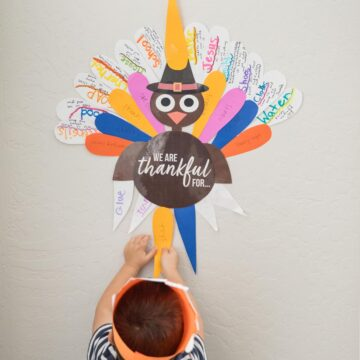 boy putting up paper turkey on wall