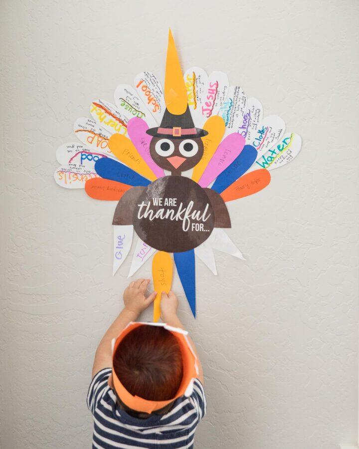 boy putting up paper turkey on wall