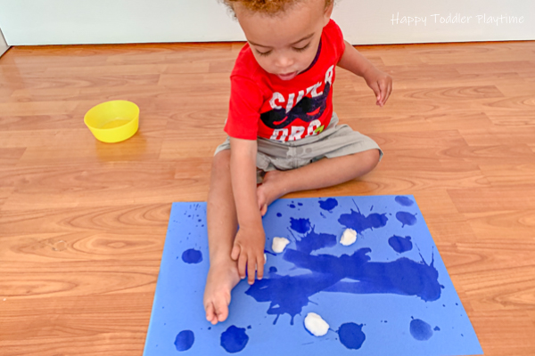 little boy painting with water and cotton balls